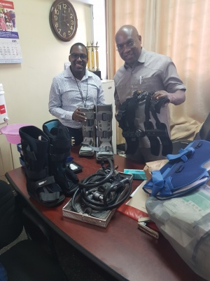 two of our tanzanian colleagues with surgical drill set and orthotic boots donated by orthocycle